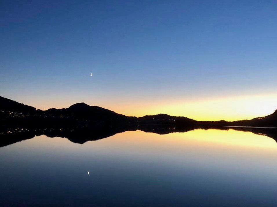 Astri S. Måkestad har òg lete seg fascinera over den fine dagen og kvelden, og ein måne på veg opp. Han speglar seg endåtil i eit blikkstille Opsangervatn.