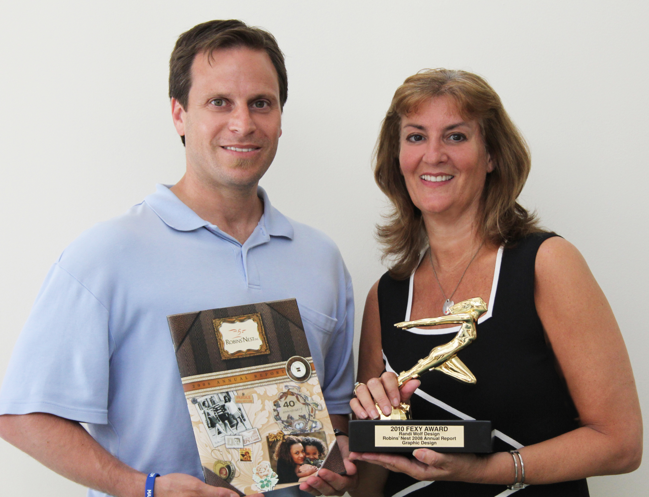 Dr. Anthony DiFabio, CEO of Robins' Nest poses with Randi Wolf after she won a Gold Award for their 40th Anniversary Annual Report.