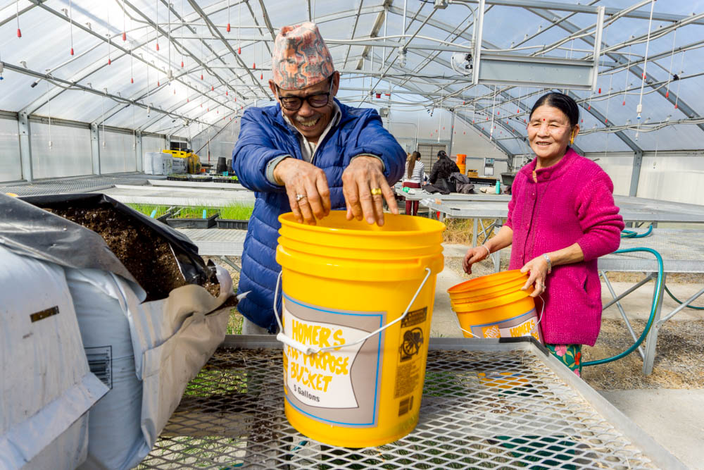 Lal Subba, Growing Together farmer, mixing potting soil in the Nashville State Community College greenhouse.