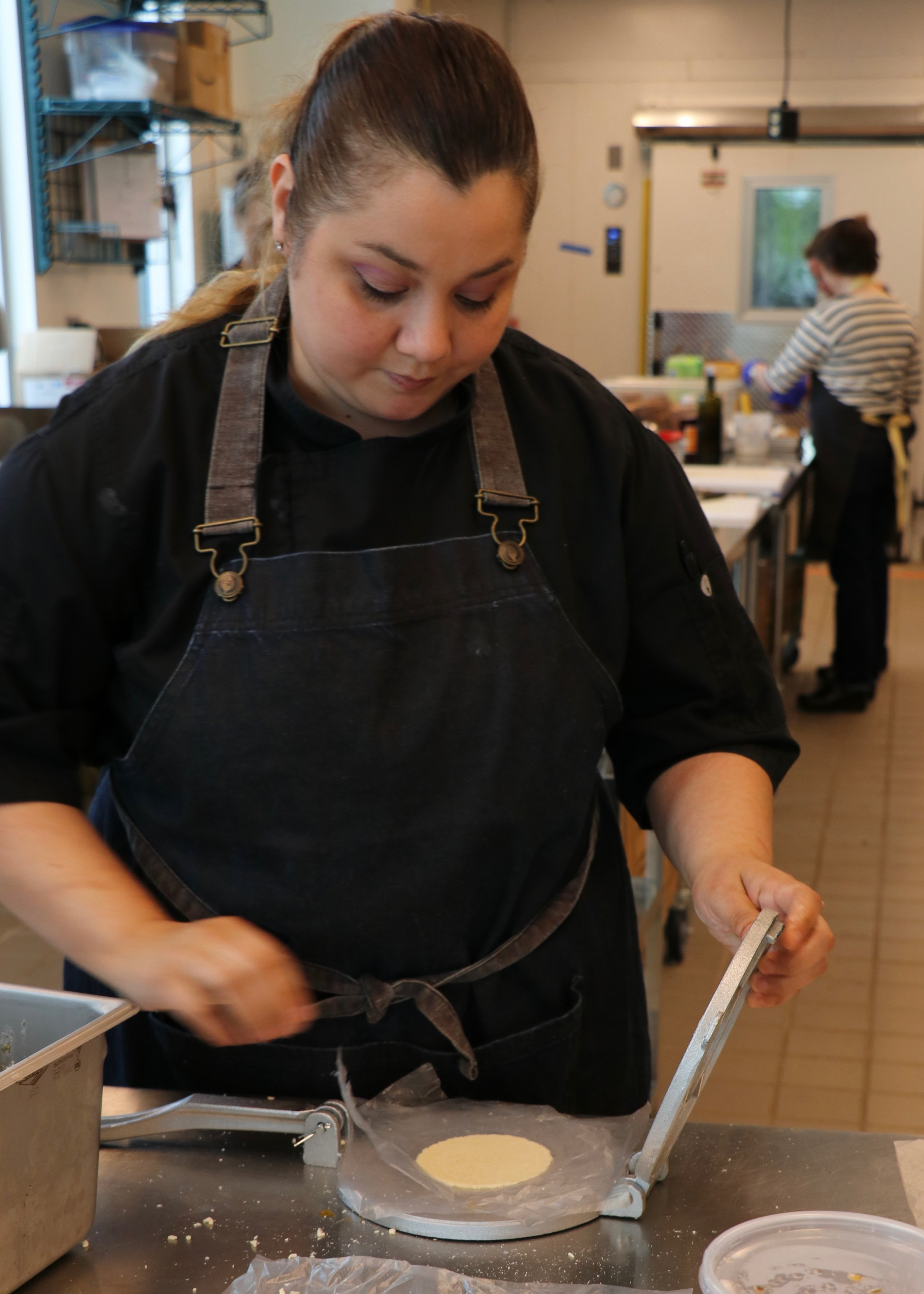 Karla Ruiz hand pressing corn tortillas for the first dish of the evening.