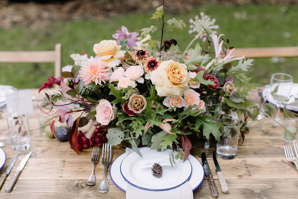 autumnal wedding centrepiece with woodland ferns and colours and garden roses