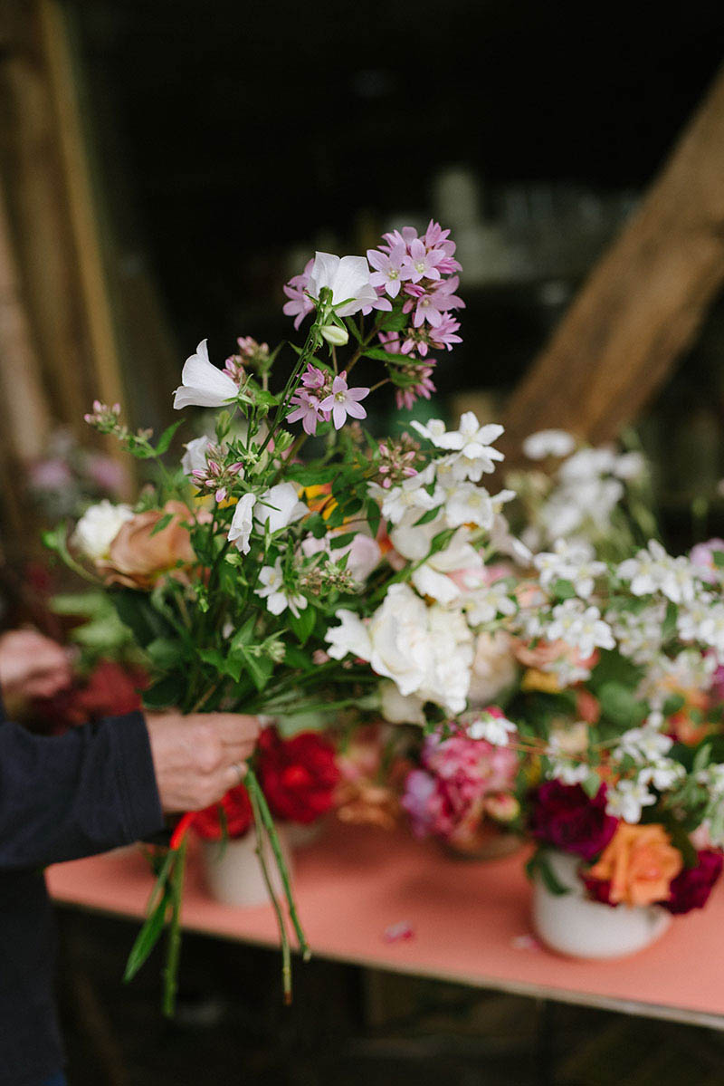 A class attendee gathering their flowers before creating a bridal bouquet.