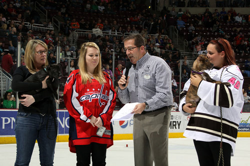 Orders for Love Board Members and volunteers talk with  Jim Jones  on the ice during a Hershey Bears Hockey game.