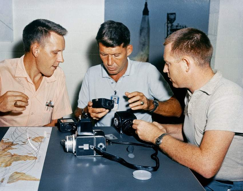 "Wally Schirra (Center) and Roland ""Red"" Williams (Right) going over how the modified camera was to be used."