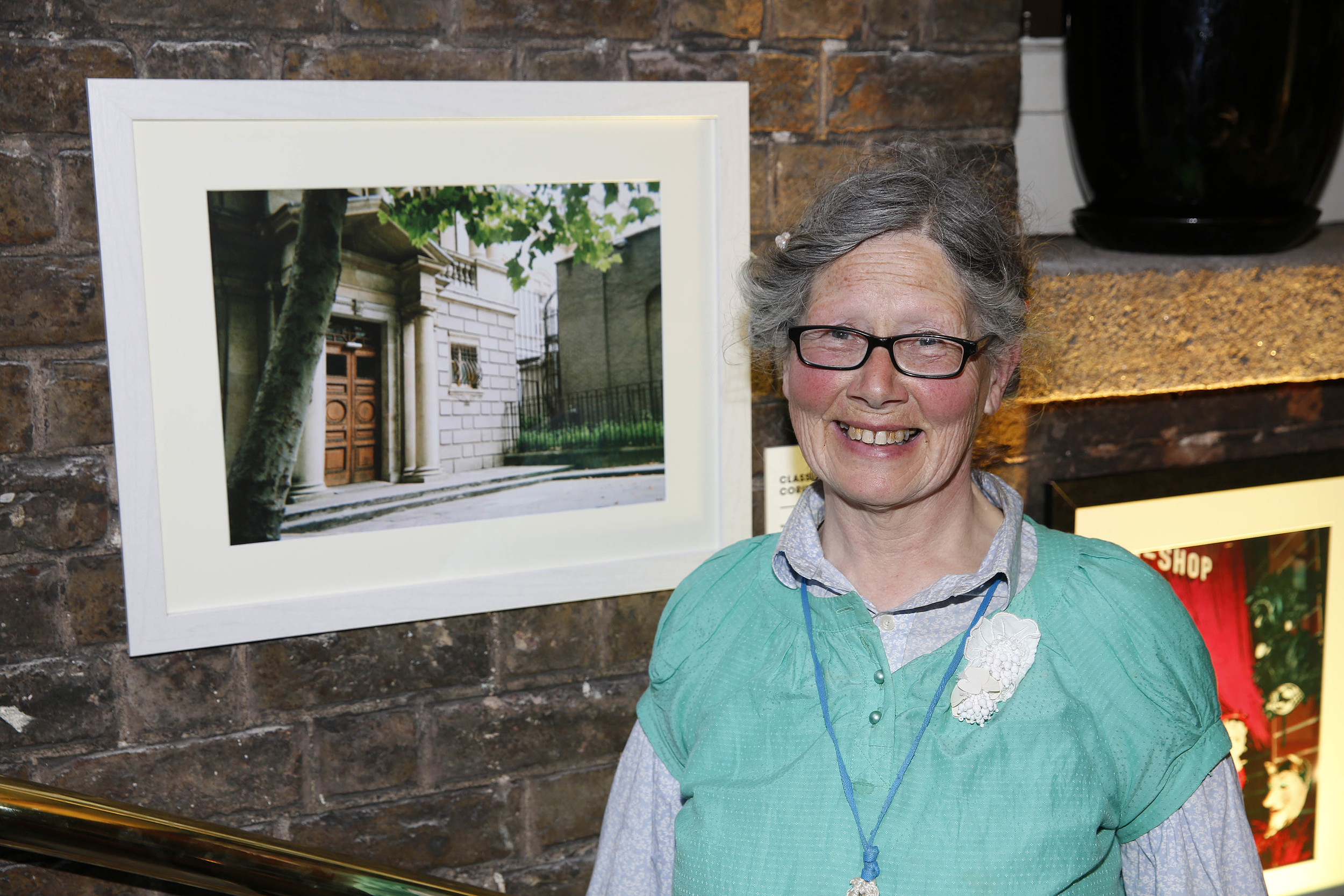 One of our IN SIGHT photographers Ramblin' Rose beside her photograph 'Classical Doors with Corinthian Pillars.'