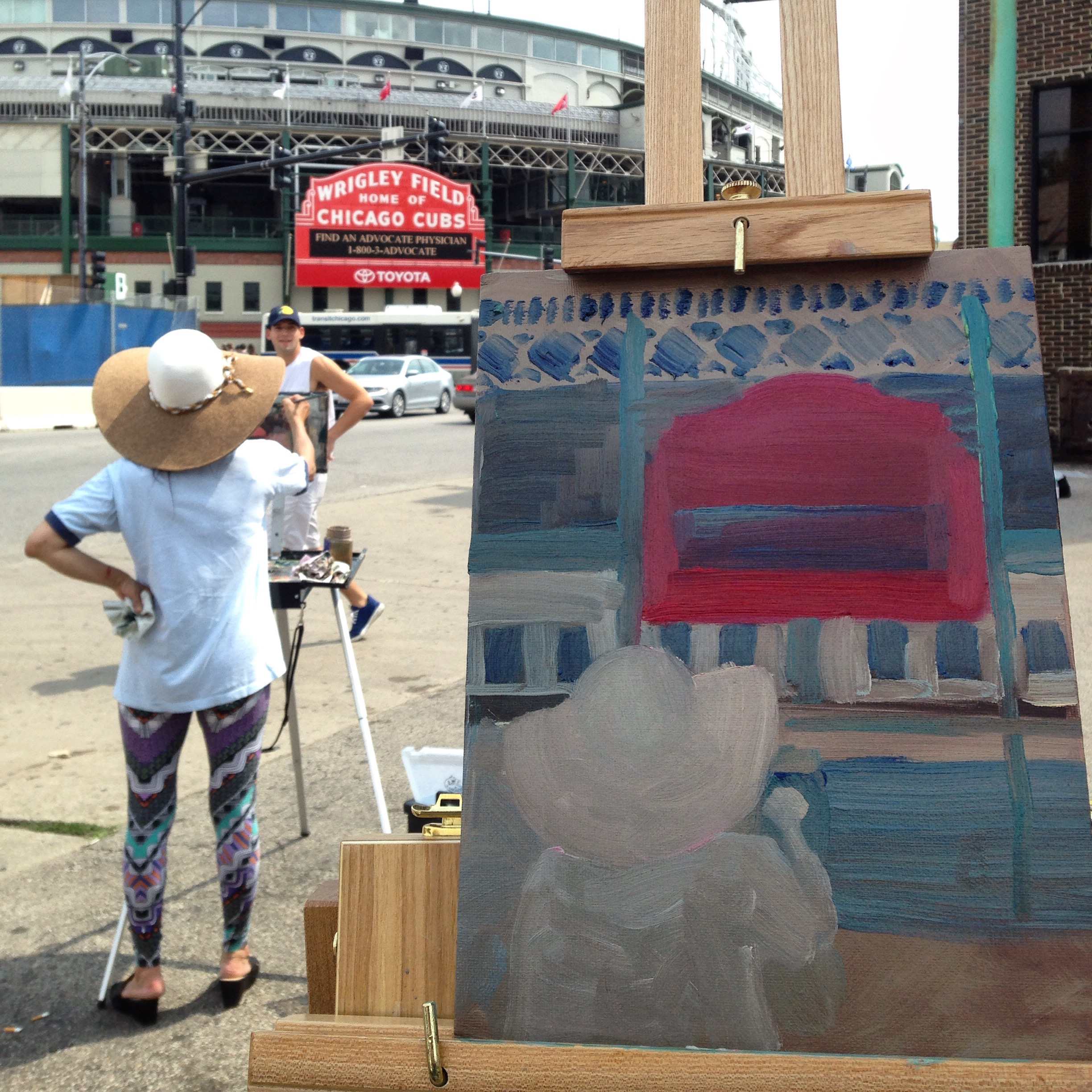 Work in progress shot of my Wrigley Field painting, with my fellow painter in the foreground. Included in this photo: friendly jogger checking us out as he went by. Not included: LOTS of folks in red shirts coming to Wrigleyville for the #MoustacheCrawl.