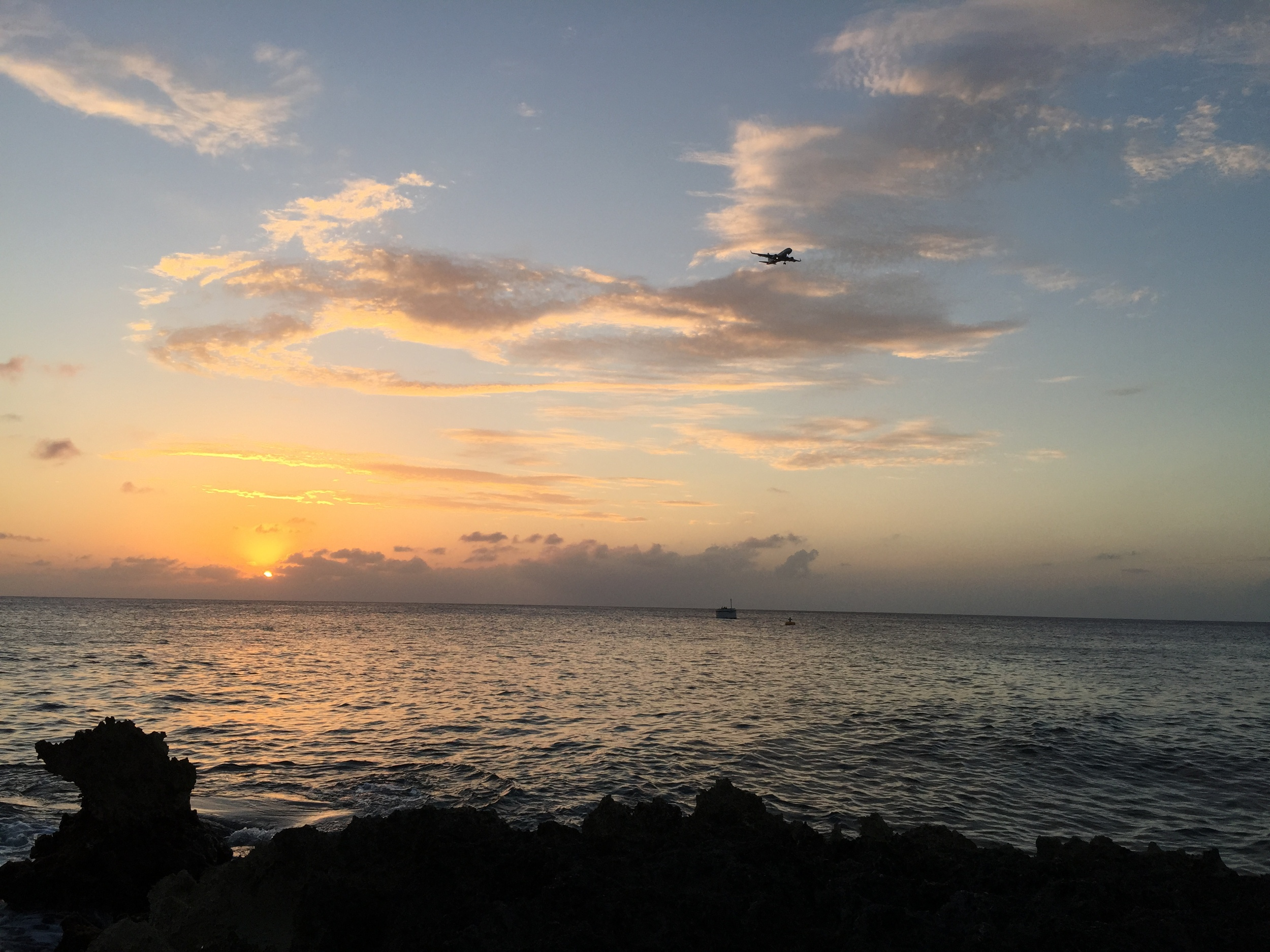 A flight comes in to land on Grand Cayman at sunset