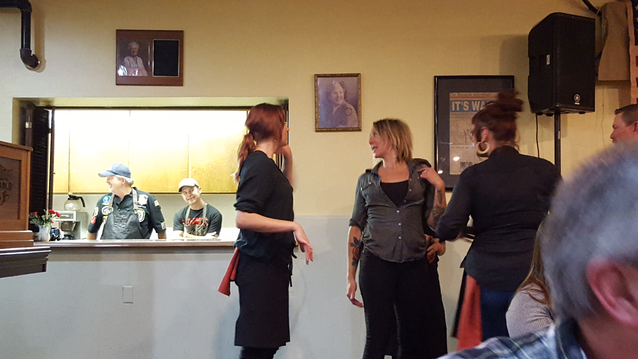 Chefs John Conley and Jamie Thousand look on while event coordinator, Eva Rupert, instructs her staff.