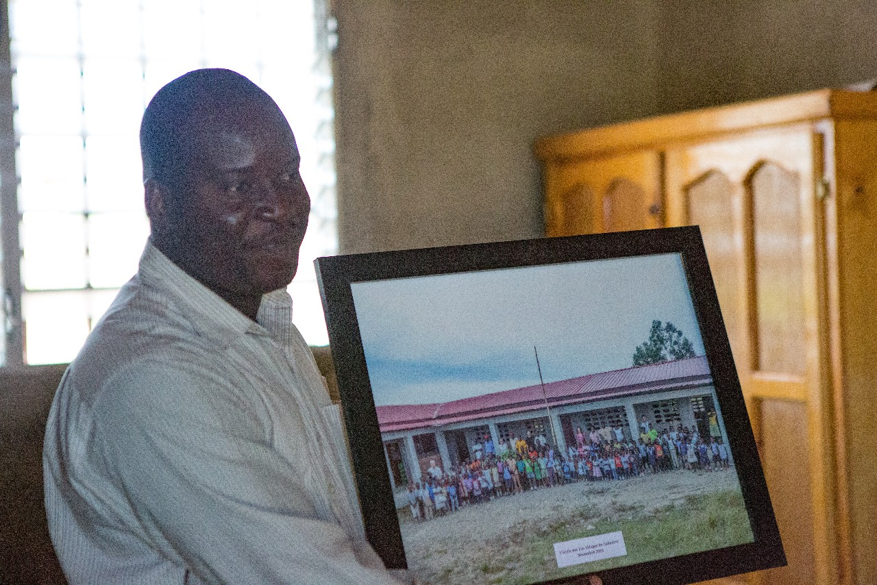 Raymond, the school principal, proudly holds the framed photo of the children of his school taken by our travel group in November 2015 and presented on this trip
