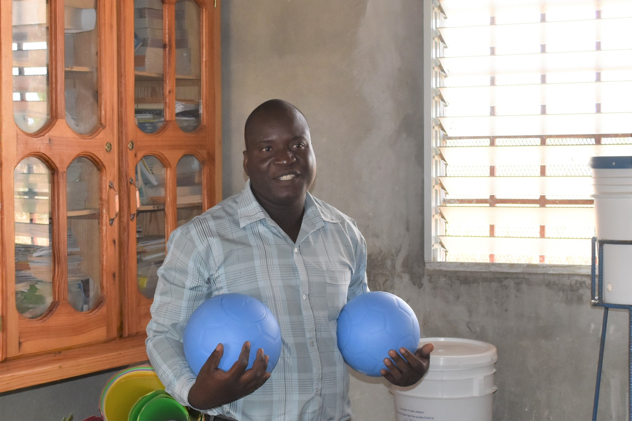 "This is principal Ramin Exil holding two of the new balls we brought to the school. These ""One World Footballs"" ( https://www.oneworldplayproject.com/  ) are solid, durable and never need inflation."