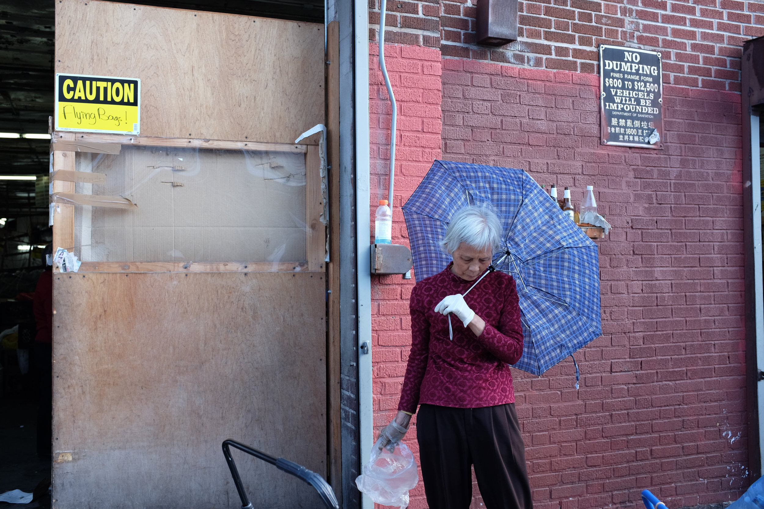A woman pauses to take a break from her work in front of the recycling center.