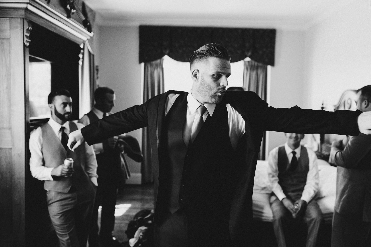 groom surrounded by his groomsmen puts on his jacket at the hote