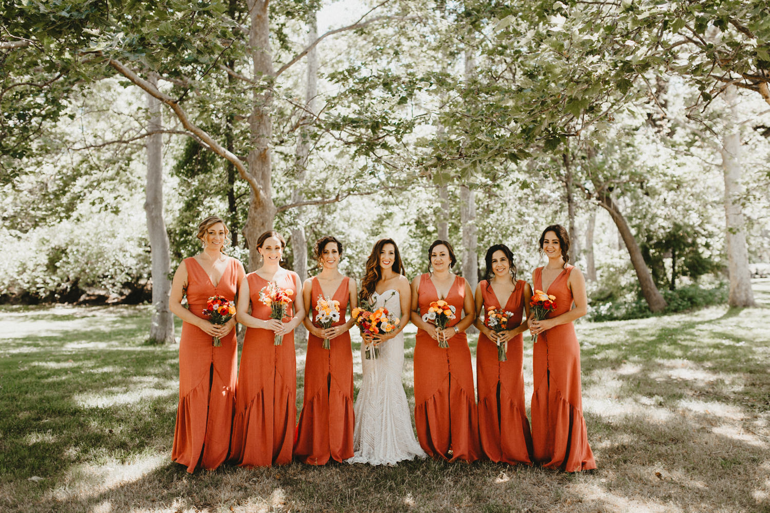 bride in white dress with bridesmaids in burnt red dresses.