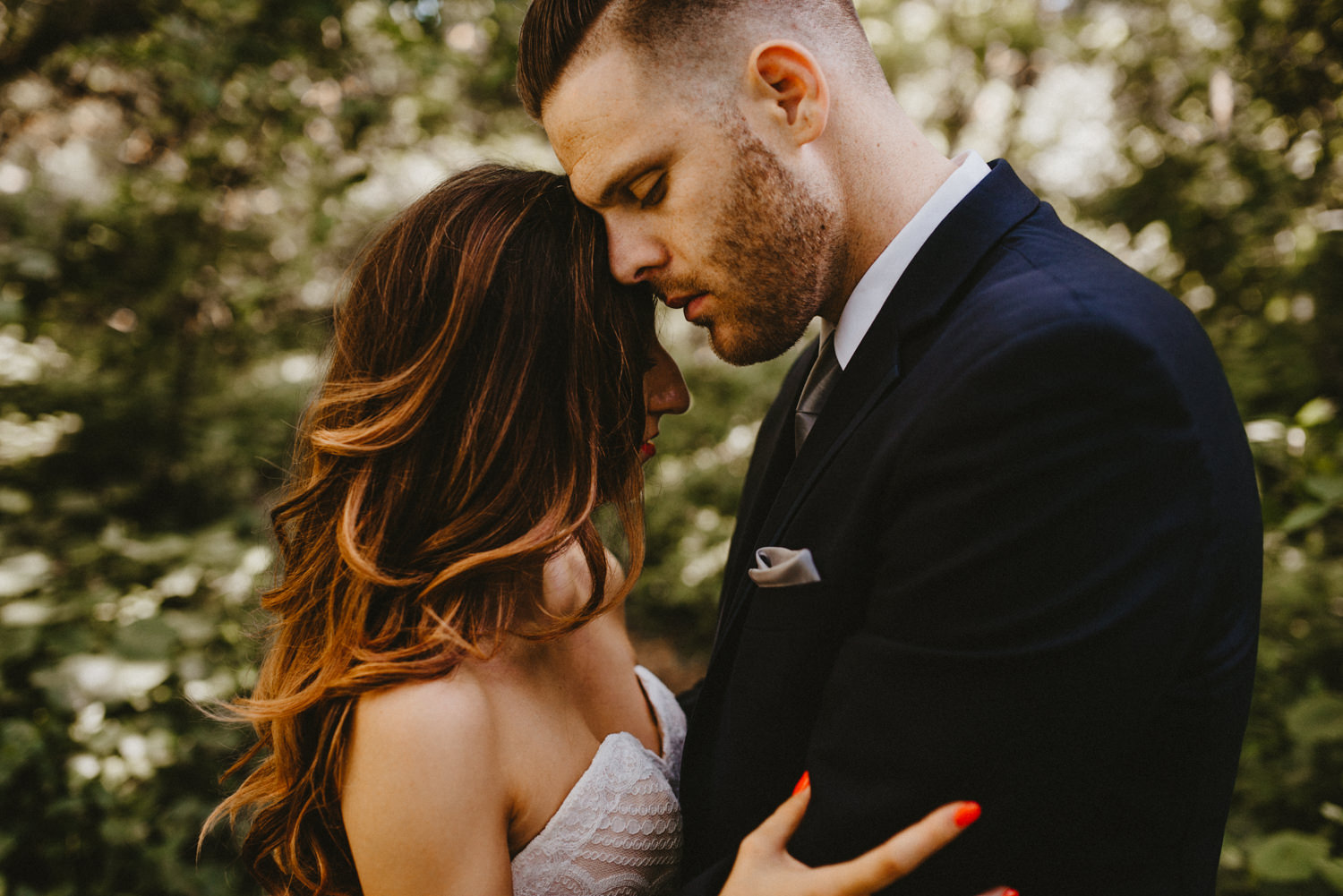 man and wife with their eyes closed heads rested together.