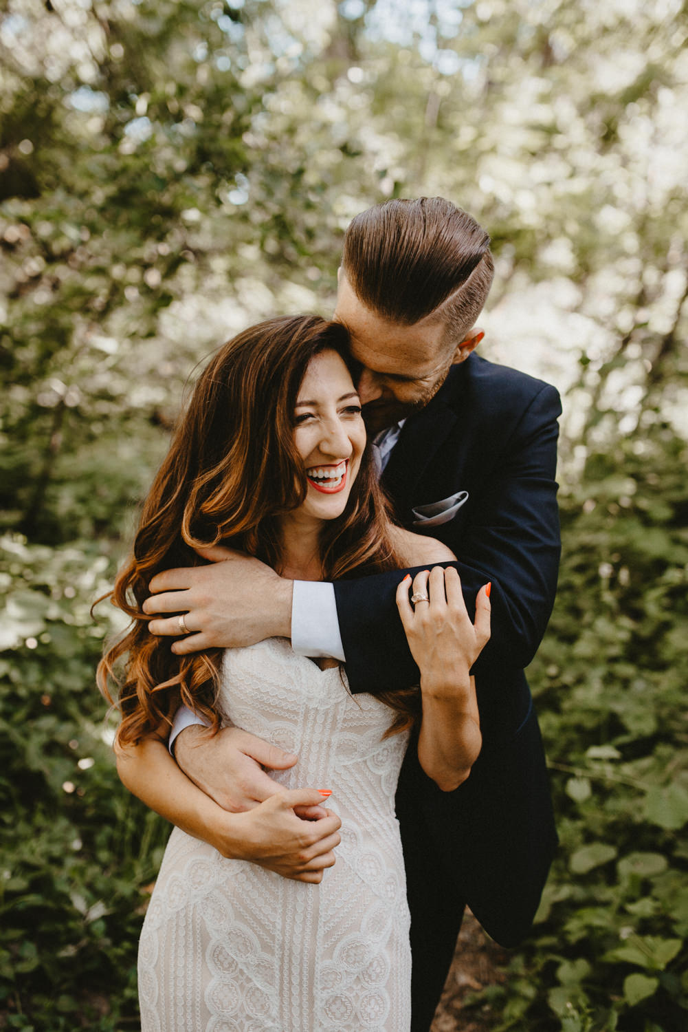 groom holds the bride as they laugh in bidwell park