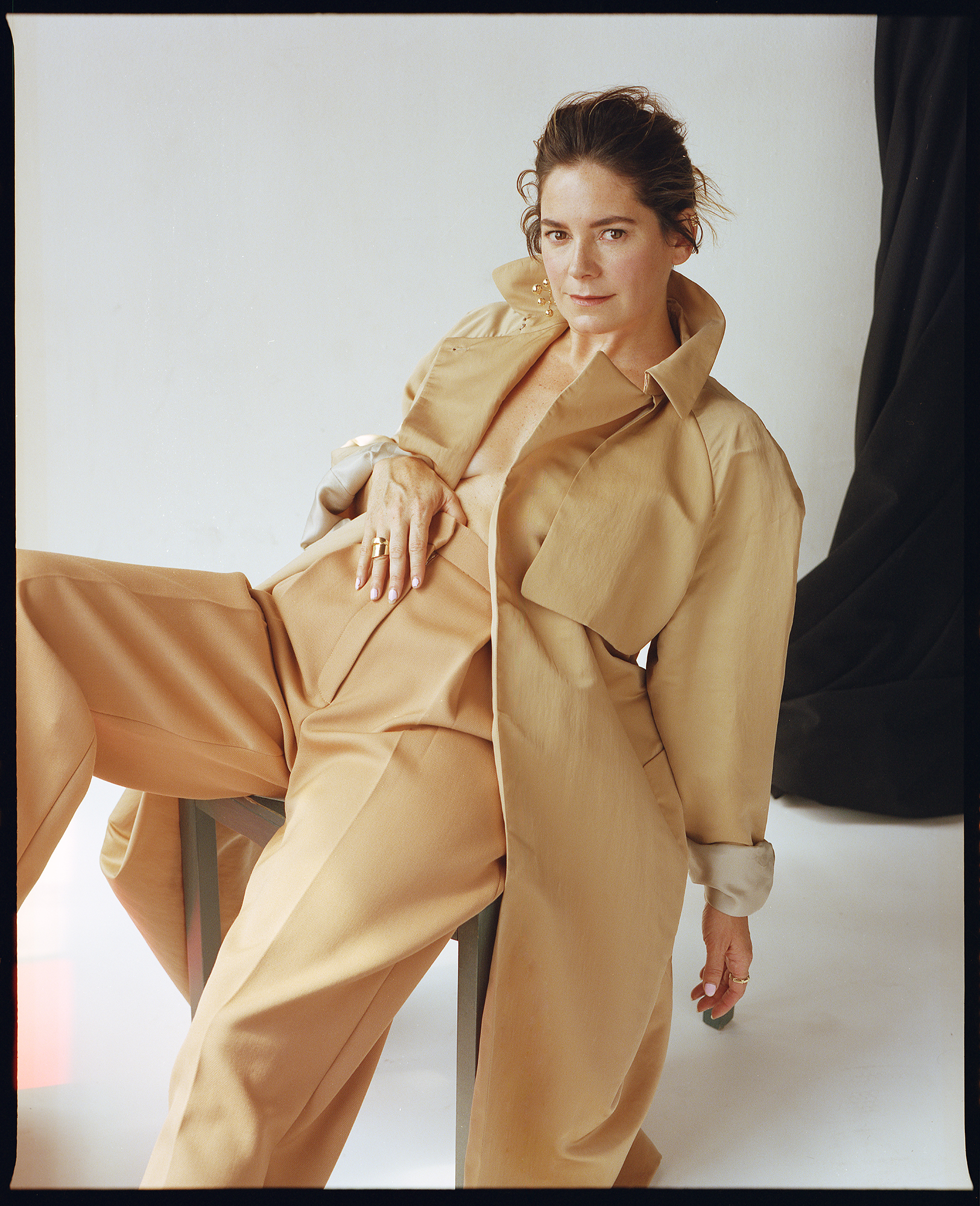 Trench and trousers by   THE ROW  ; Jewelry by   JENNIFER FISHER