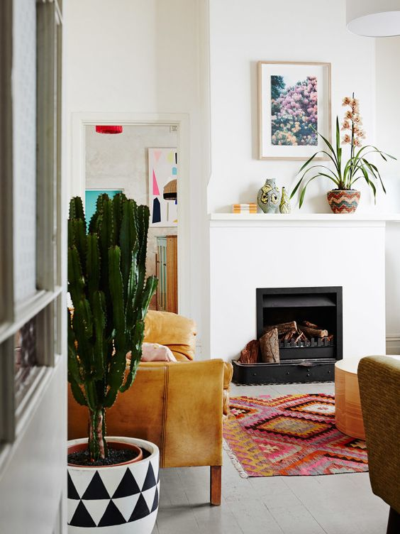 The color and pattern of the selected pieces really fill this space with life. The floors, walls, and fireplace are all white/neutral - a palette that allows smaller pieces like the vases to speak.