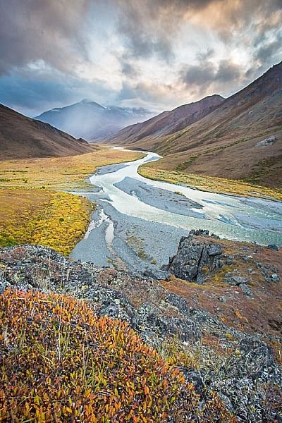 Осінні кольори, що близько до краю знімка, є нашою відправною точкою. Глядача скеровано до звивистої річки, а тоді до бурхливих гір за її межами.