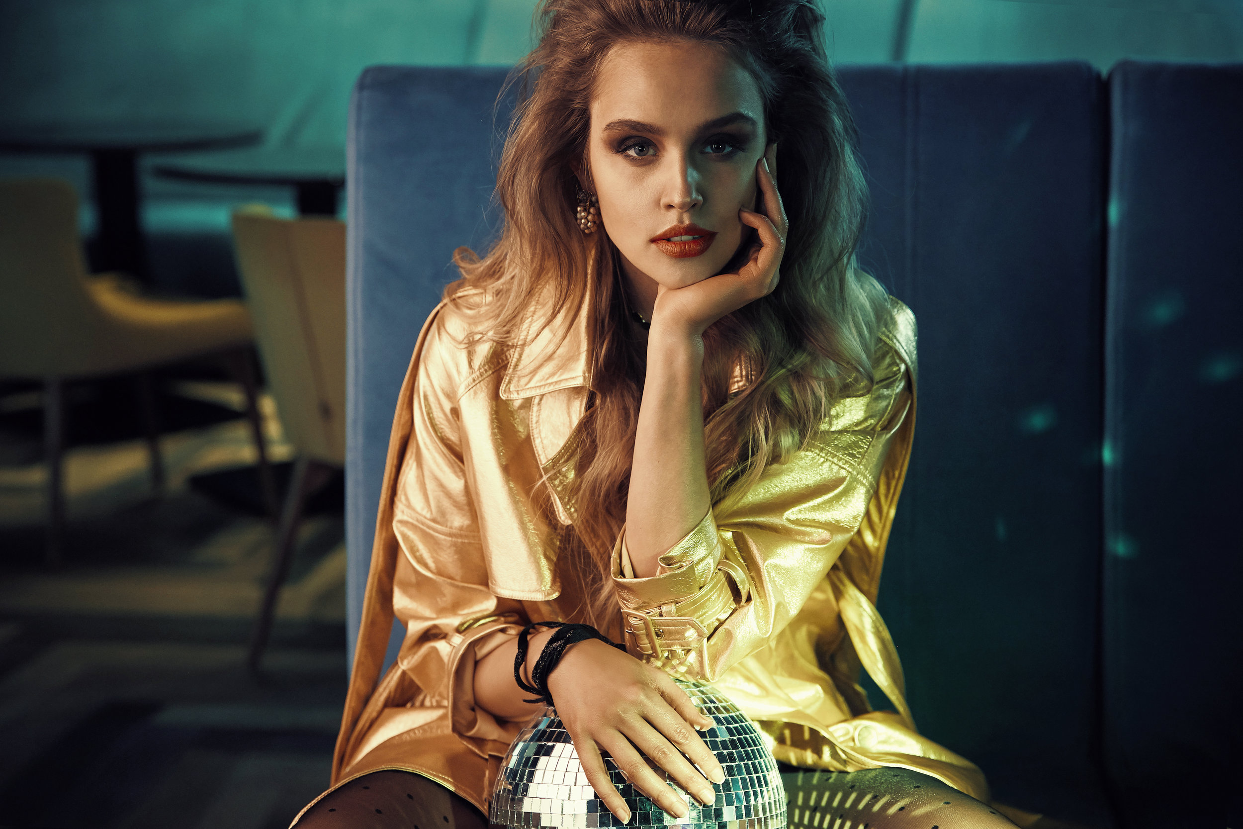 Luxury portrait of beautiful young woman in gold trench coat, sitting on blue couch with disco ball. Retro style