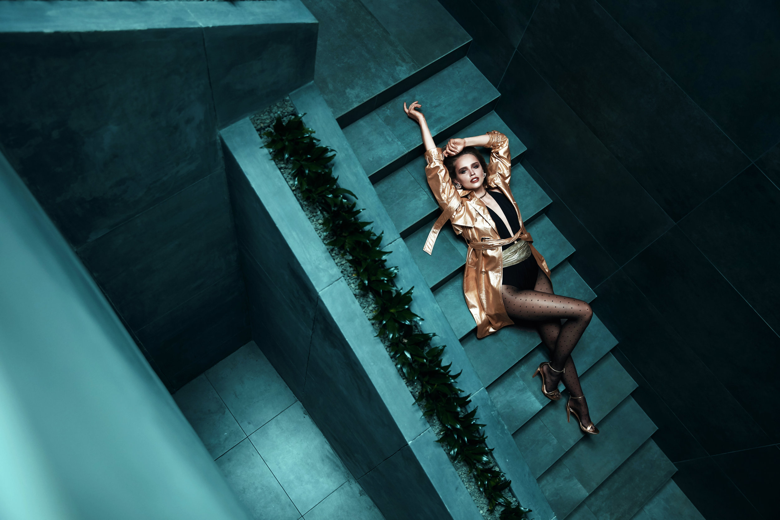 Amazing young woman in gold trench coat, black bodysuit with gold belt and in black polka dot tights is lying on the turquoise stairs