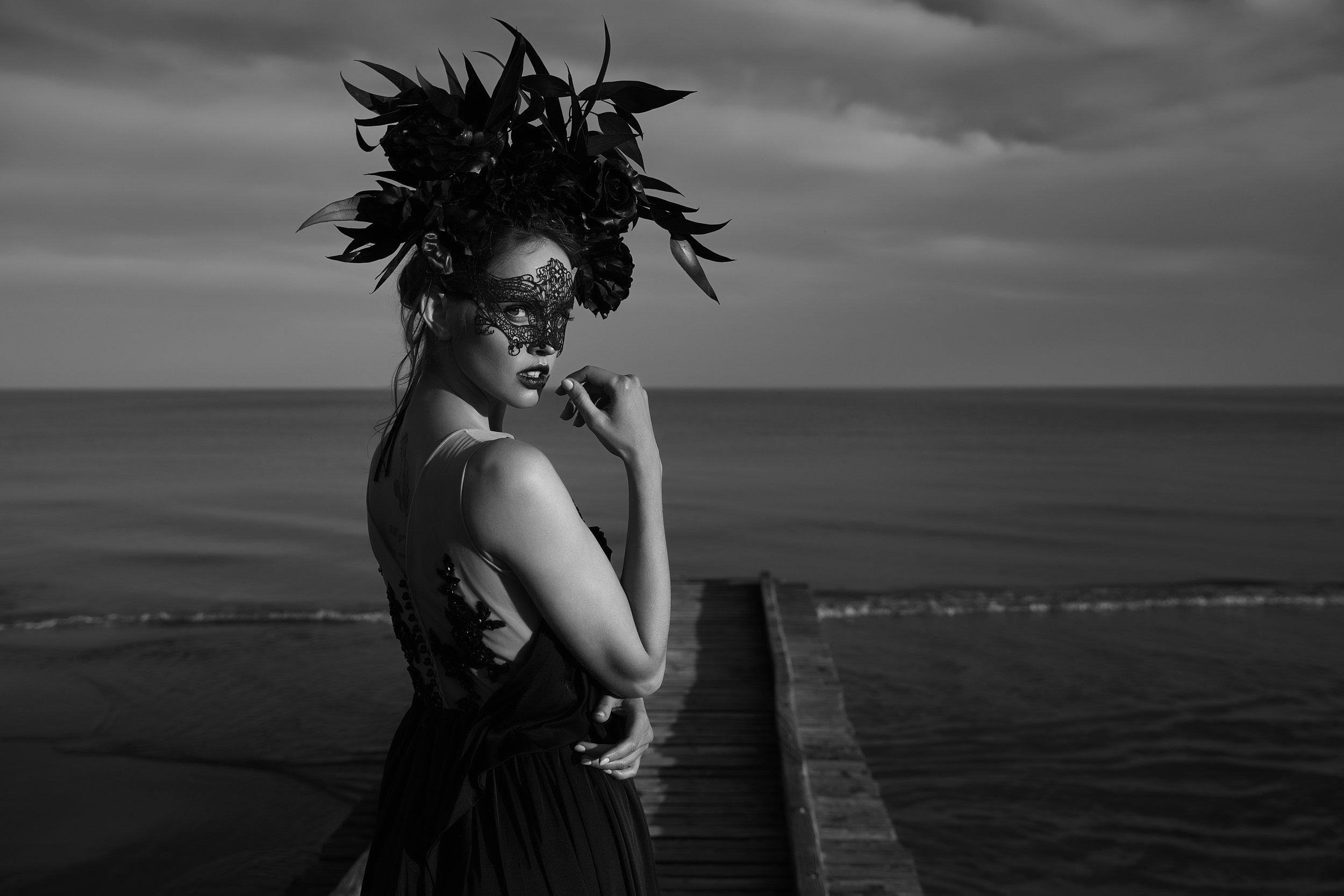 Black and white dramatic portrait of beautiful emotional woman with black lace mask on face and big floral crown on head stands on wooden pier. Dark clouds and sea on background