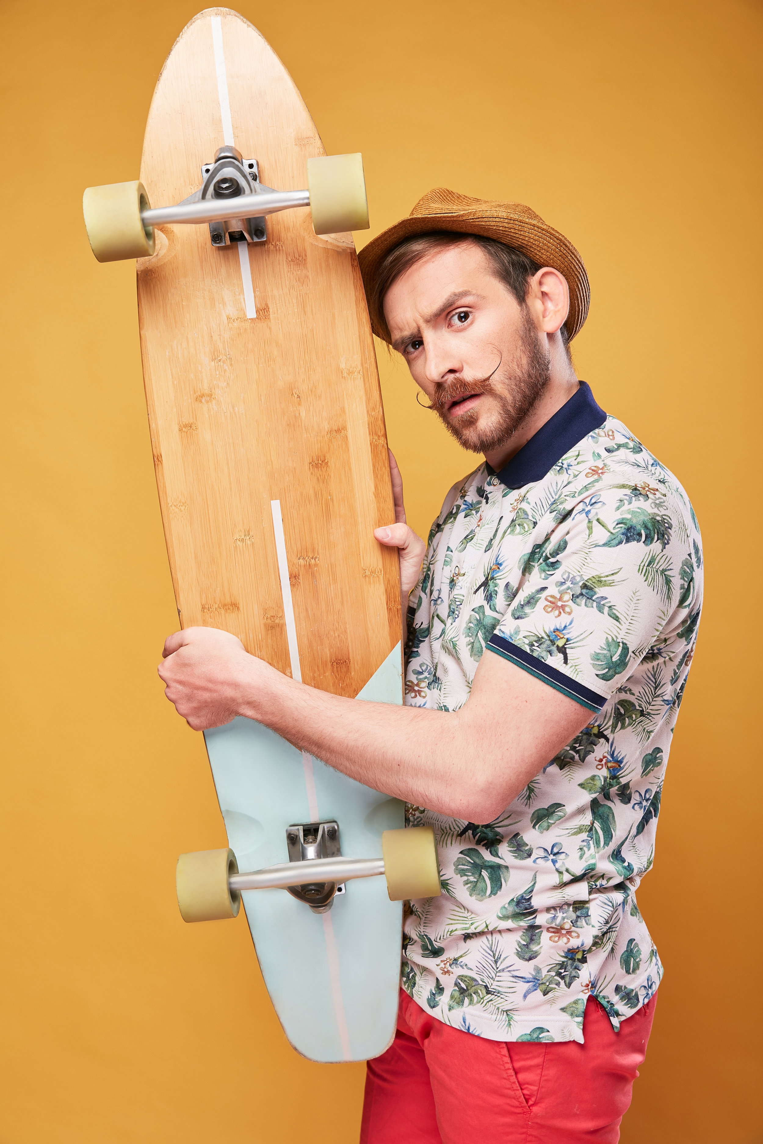 Young man with handlebar mustache and raised eyebrow, dressed in tropical print polo shirt, red shorts and straw hat, with longboard in hands. Studio shot with yellow background
