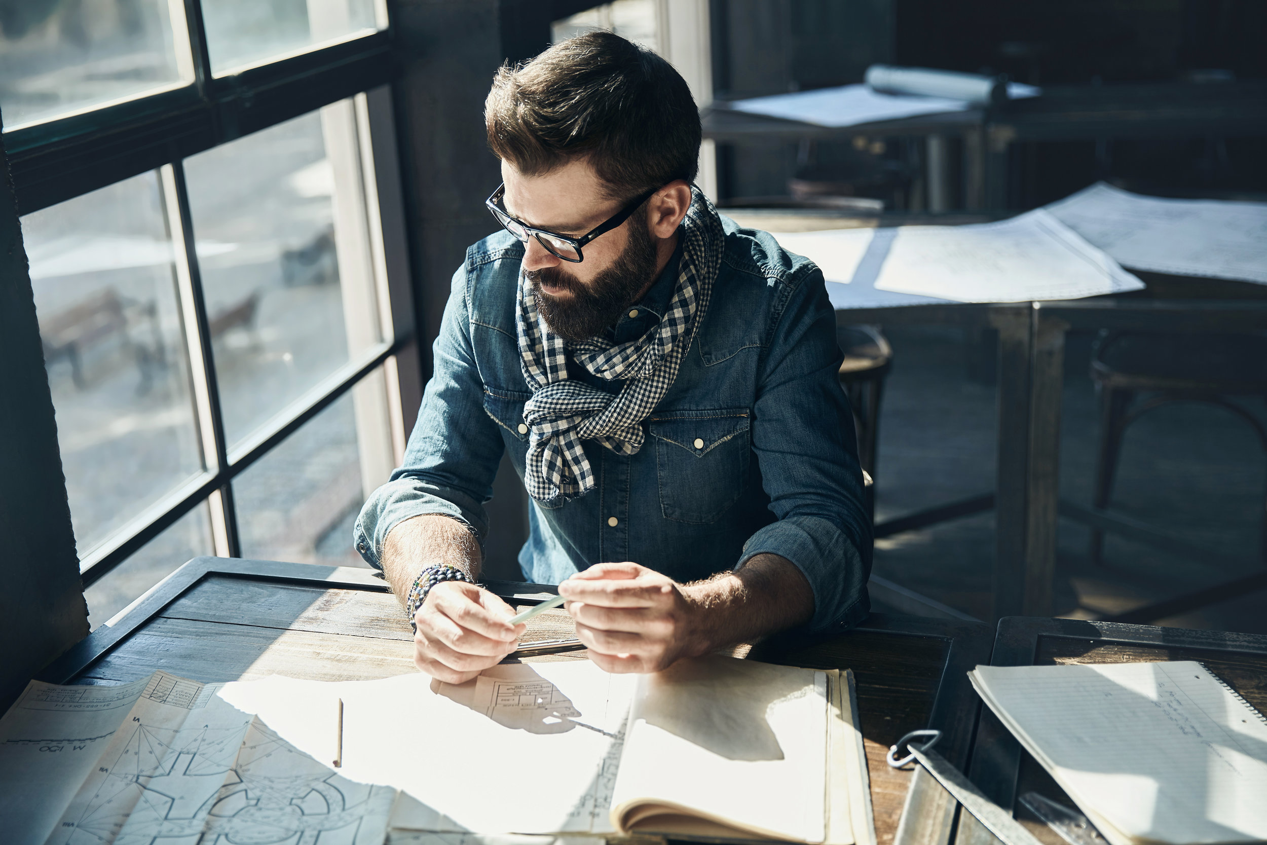 Man architect with dark hair and beard, weared in denim jacket, scarf and glasses is sitting in the modern office near the window with architectural plan on the table