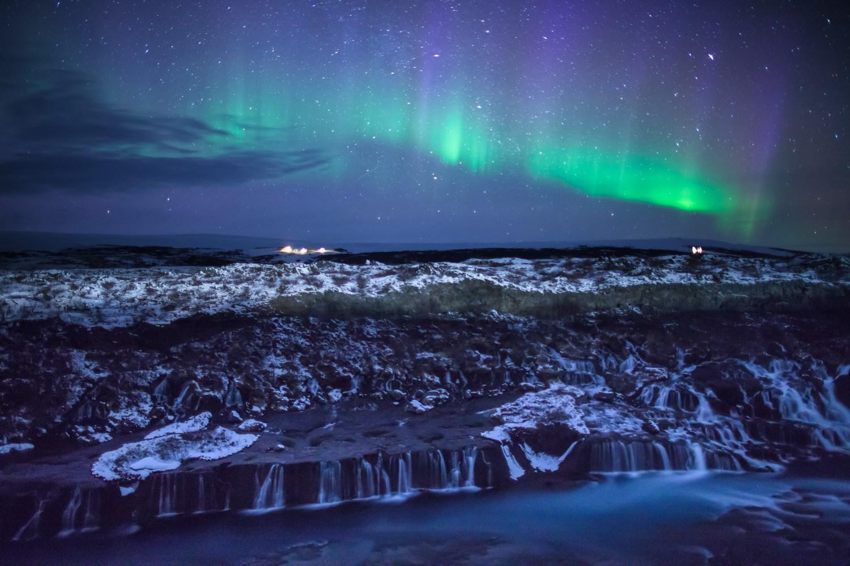 Northern lights dance over Hraunfossar waterfall, Iceland