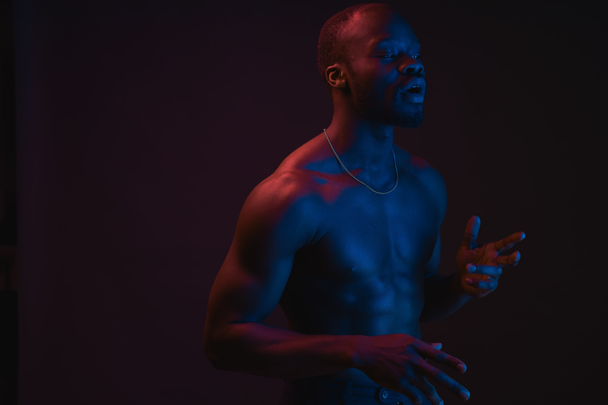 Red and blue lighted portrait of young and sexy muscular shirtless man with neck chain.