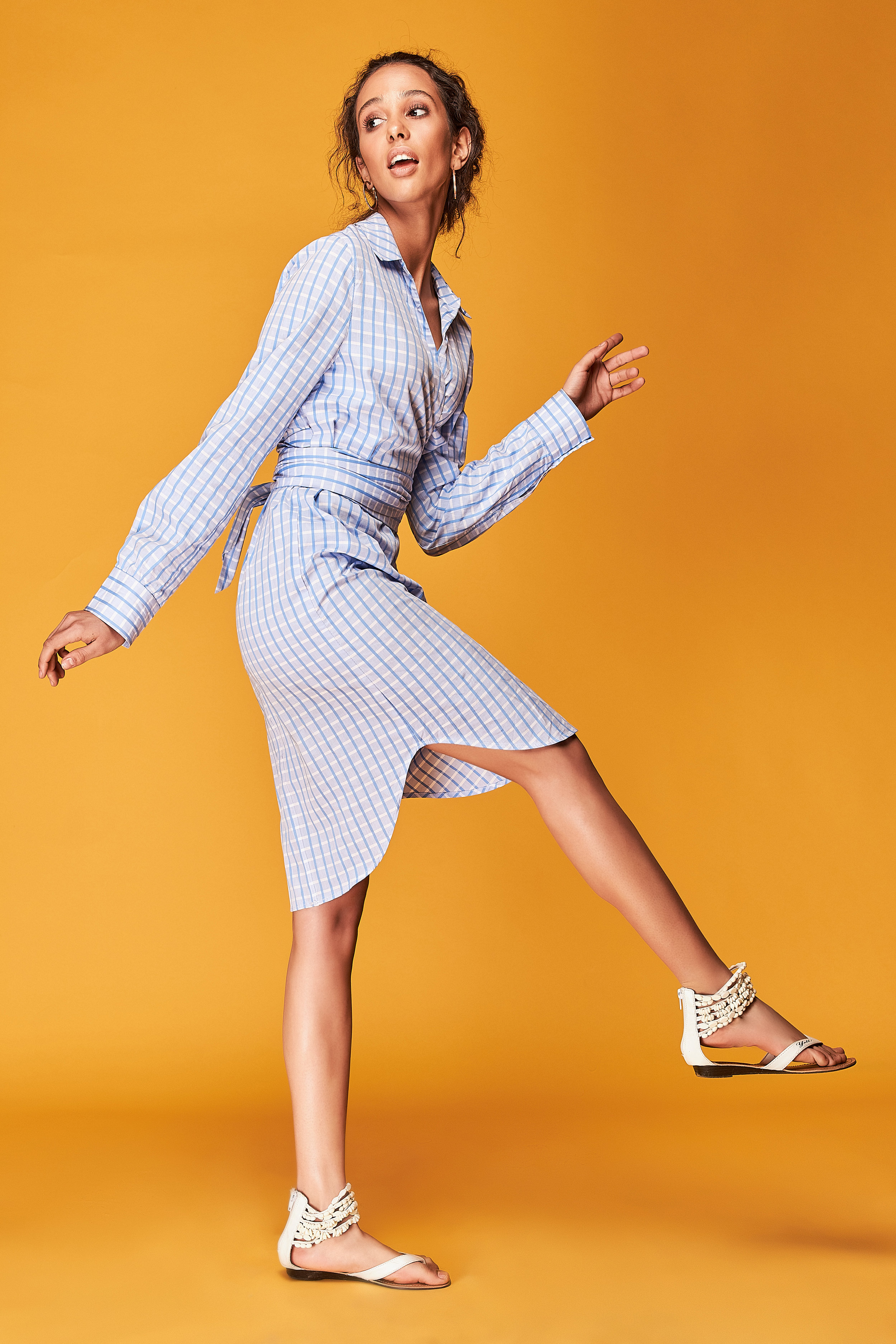 Full length portrait of tanned female model with curly brown hair, dressed in blue plaid shirt dress. Dynamic poses. Orange background