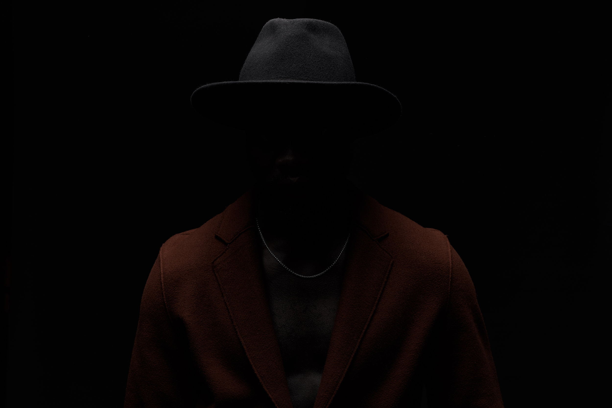 Man in the dark. Dark key portrait of black man on black background. Man dressed in black hat and brown coat