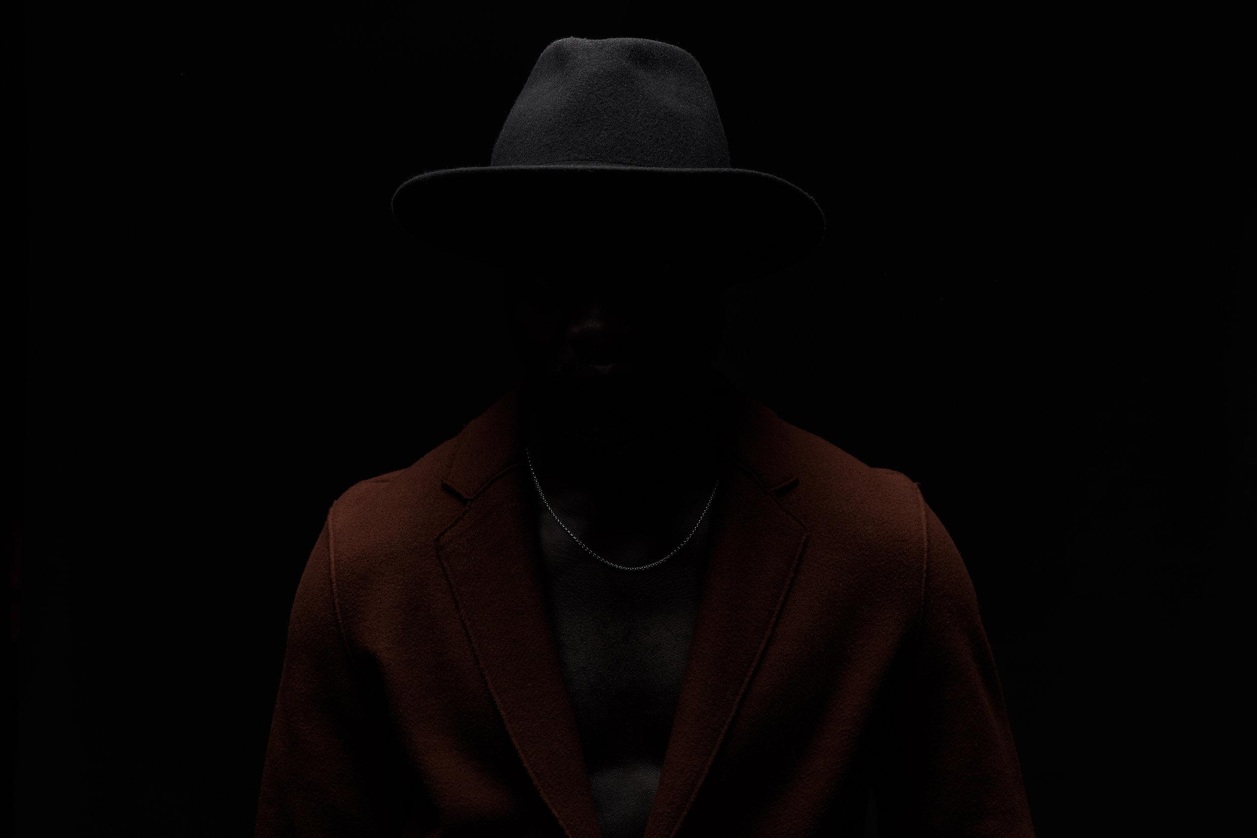 Man in the dark. Dark key portrait of black man on black background. Man dressed in black hat and brown coat