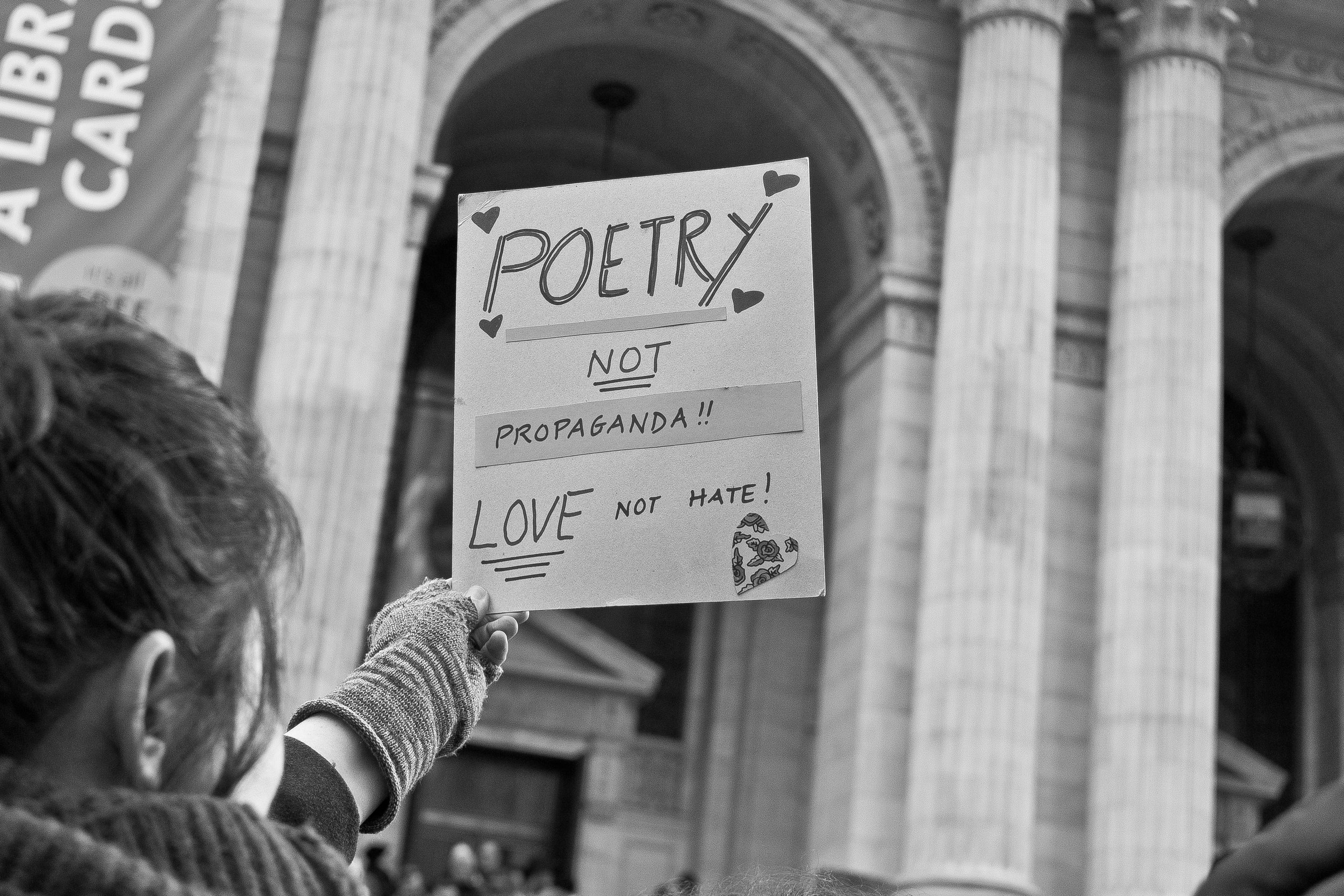 A poet holds up a sign outside of the New York Public Library during the Writers Resist action.
