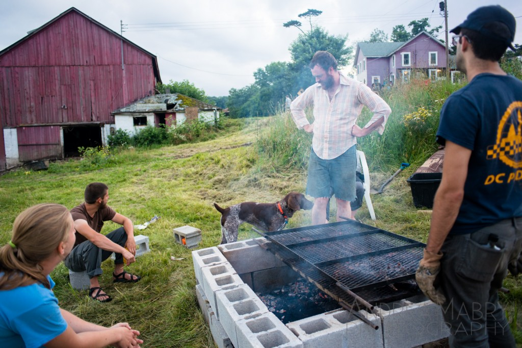 Farmer Nick talks with Dart while the pig roasts. As we prepare to eat pig, inside the barn there are piglets eating.