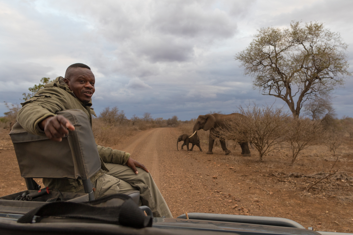 """My good friend and colleague Sunday Ndlovu poses with some elephants in the background. Sunday's last name,  Ndlovu , means """"elephant"""" … so I find this photo rather fitting."""