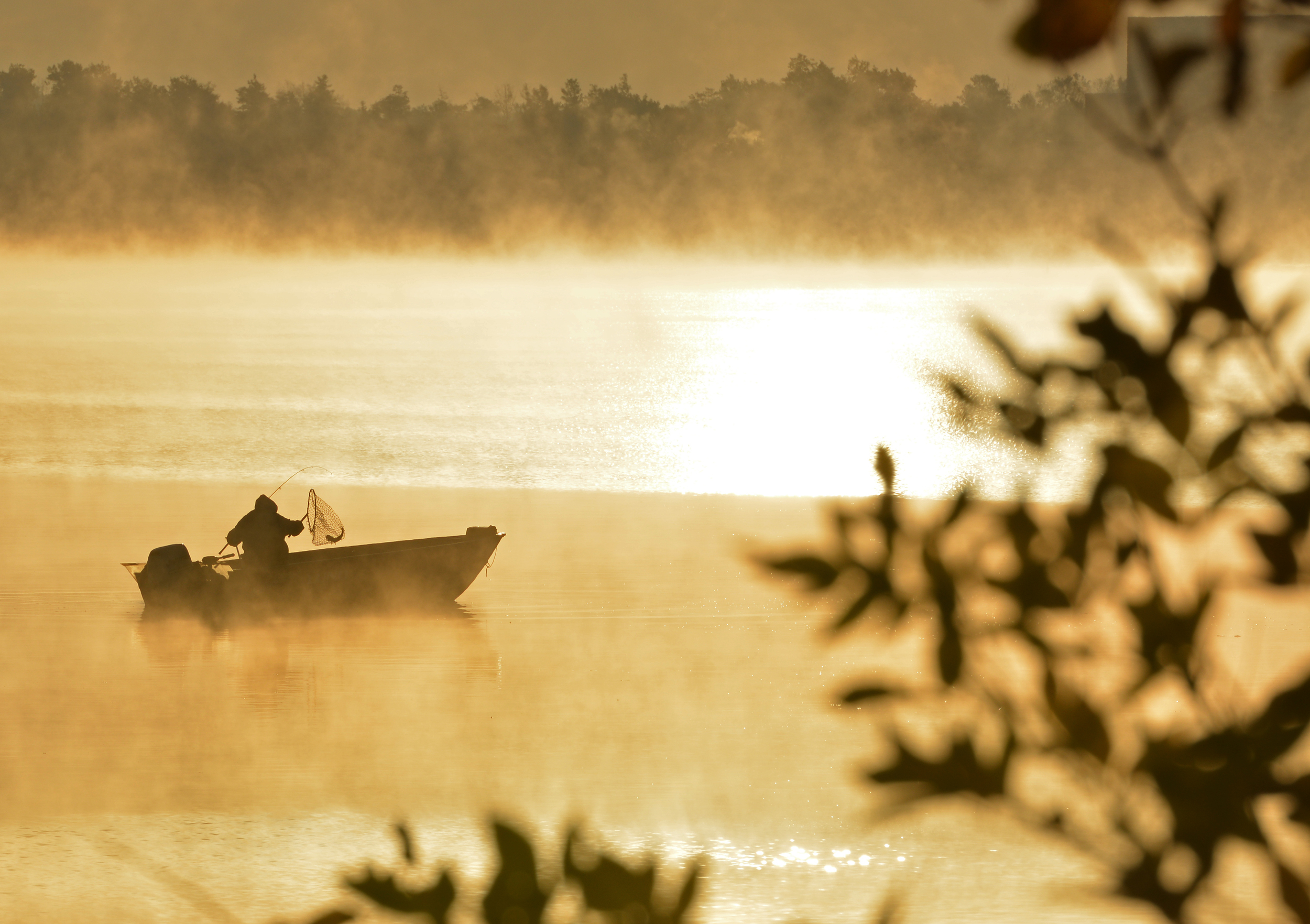 A fisherman nets a fish during a spectacular October sunrise over Lake Bemidji.