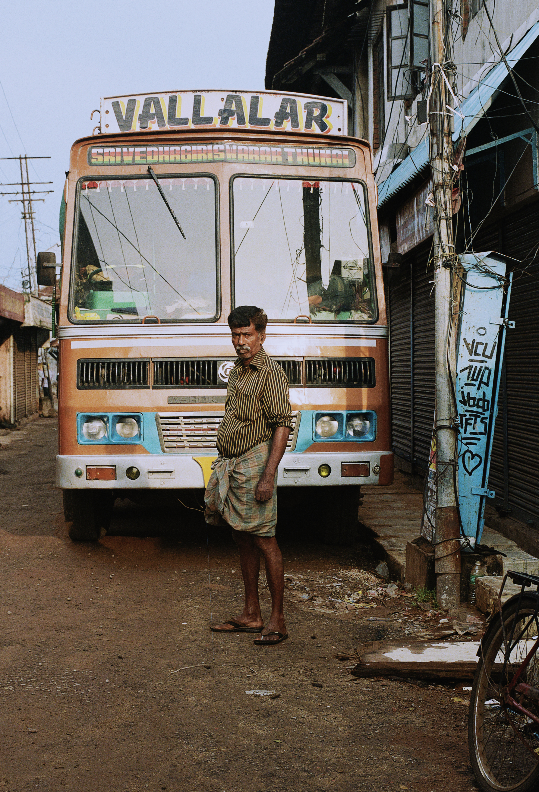 Man in front of bus on busy market street in Fort Kochi.