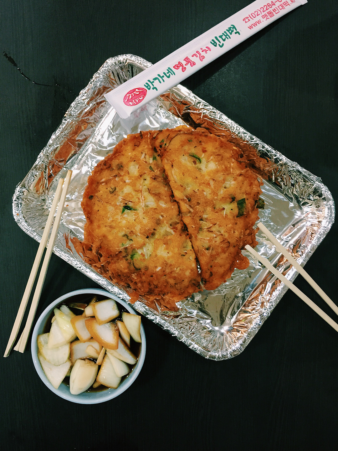 """The most popular food at Gwangjang Market is their """"jeon,"""" or pancake. It's a dish that was meant to be eaten on rainy days, but is now enjoyed any day of the year. My absolute favorite is the Nokdu Jeon, or mung bean pancakes. It's crispy on the outside and soft on the inside, making it the ultimate savory treat! Dip it in the soy sauce and enjoy it with the soy sauce marinated onions. The combo is a match made in heaven! <3"""