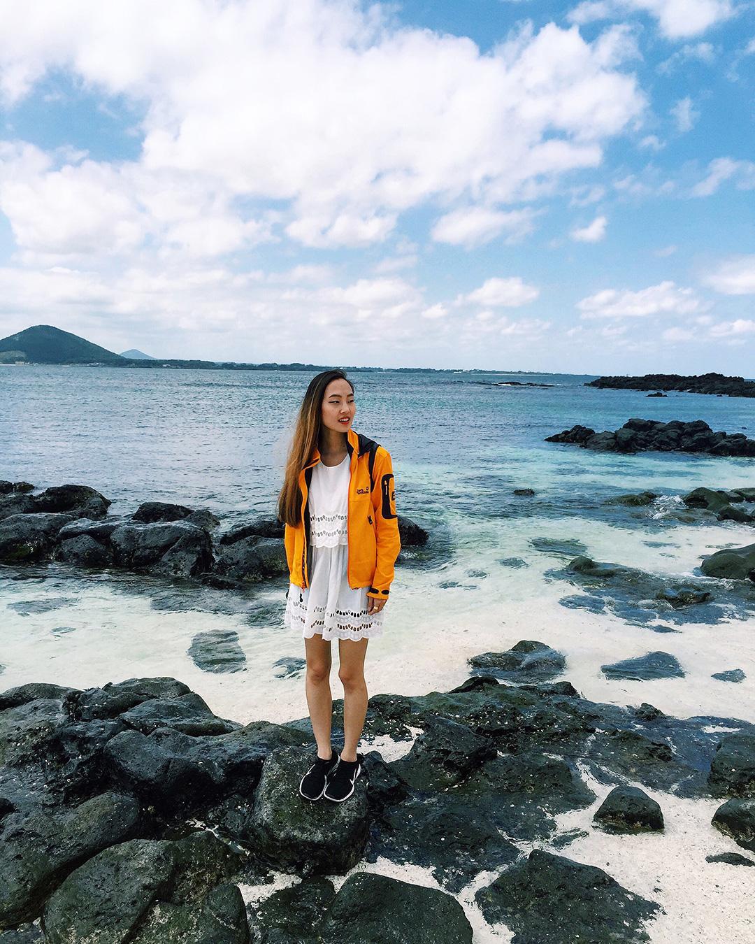 Enjoying the beautiful Seobinbaeksa Beach with its contrasting black lava rocks and white coral sands.
