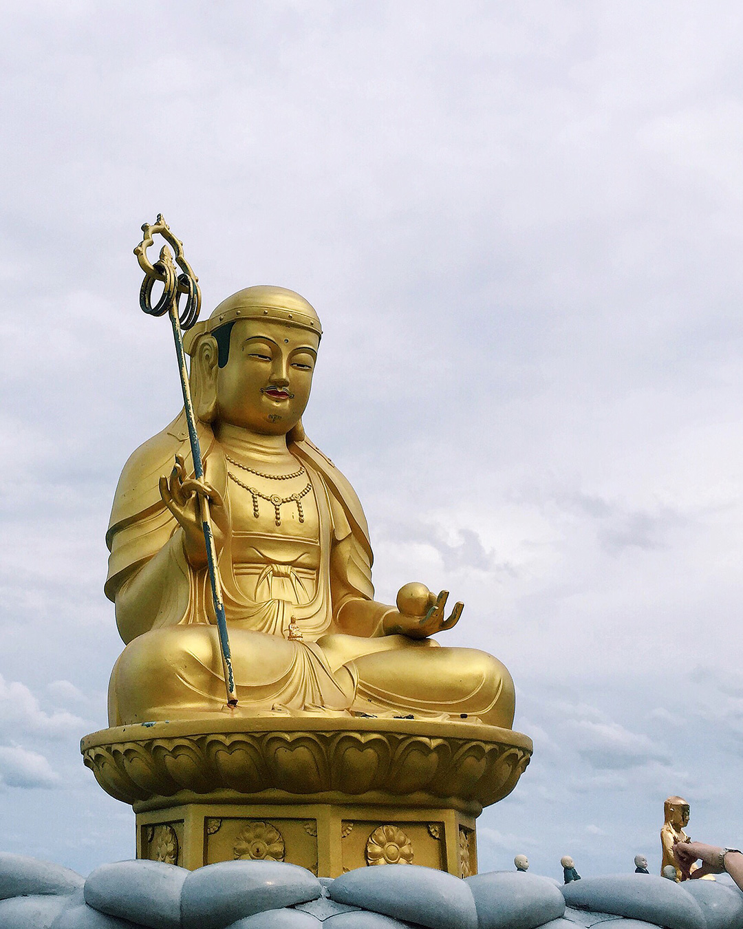 This golden Buddha sits right on the coastline while waves hit the shore right at its base.