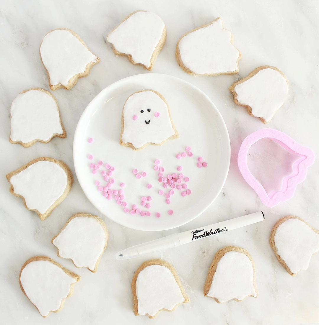 STEP 3 - Once the icing has somewhat solidified, use an edible black marker such as this one by Wilton,to draw on cute eyes and a smile. Get creative with your faces, and use emojis as your inspiration!Then press two pink confetti sprinkles as