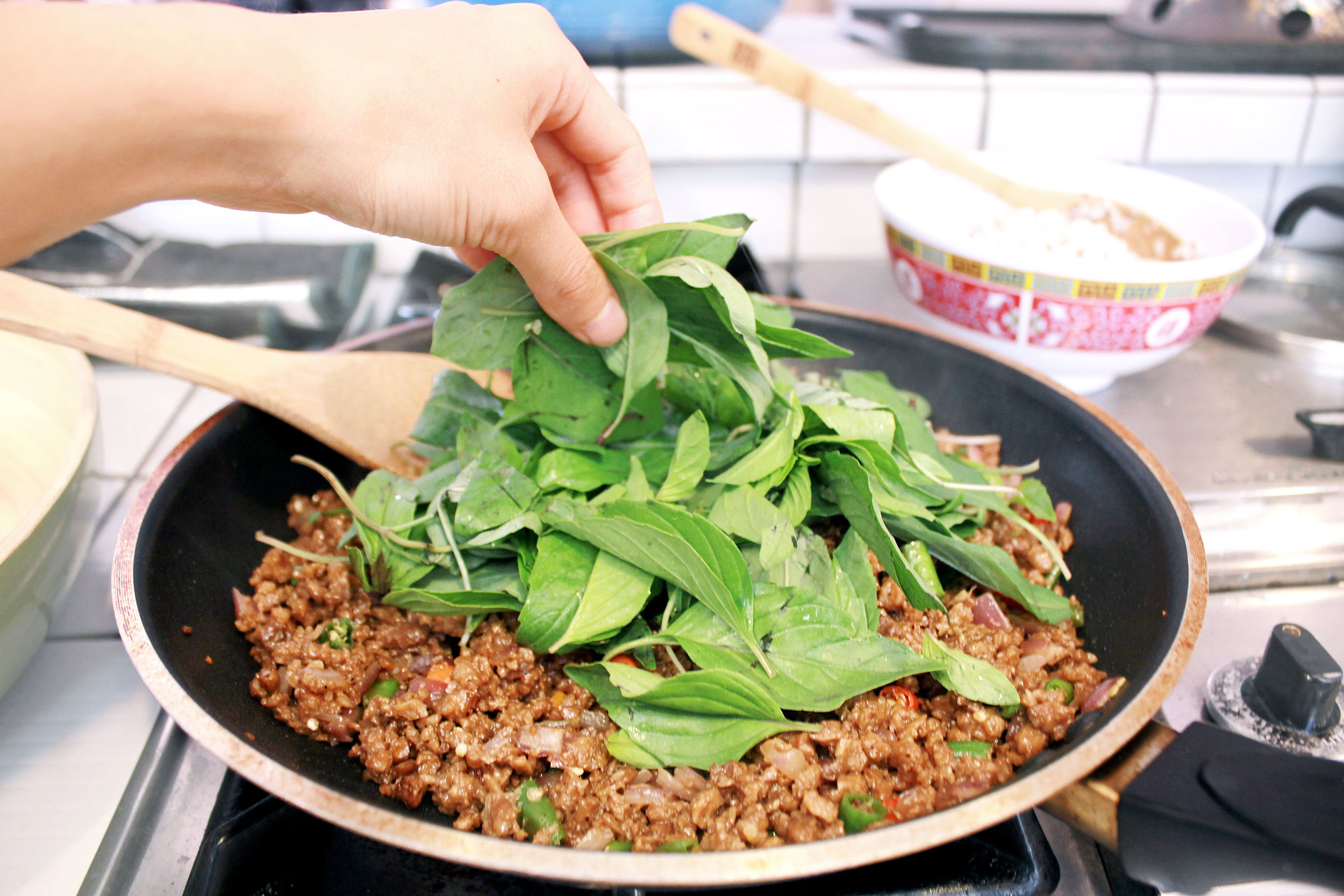 STEP 4 - Turn off the heat, add Thai basil, and mix in. The heat will wilt the basil quickly.