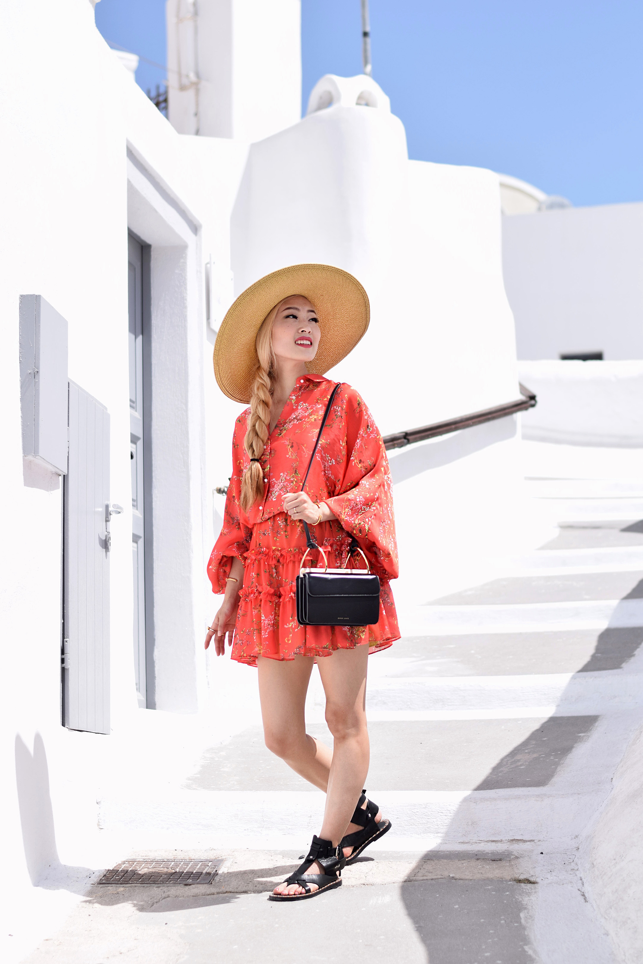 Floral dresses aren't only for spring, they're perfect for summer as well. My Santorini Lookbook 2 brings flower power to the forefront with this amazing floral dress by Alexis. This is the season where flowers are in full bloom, and I felt like this bold red dress went perfectly with all the flowers in Santorini. | #ontheblog | #SantoriniFashion | #travelSantorini | #Greece | #summerfashion | #traveloutfit | Isabel Marant | Nine West | #floraldress | #summerdress |