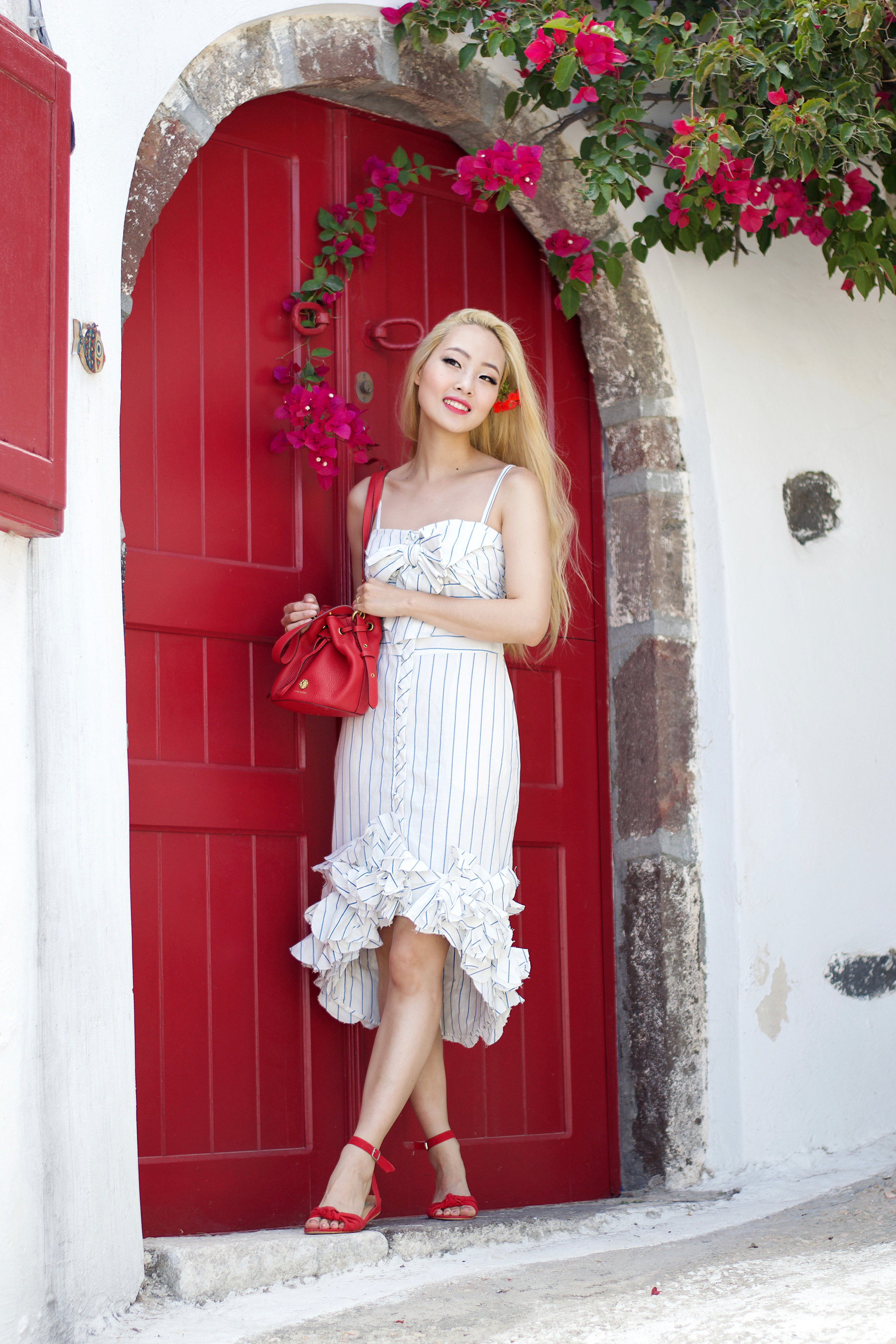 In the sixth and last look from my trip I created a look inspired by the blue and white architecture of Santorini, and the red bougainvillea blooming everywhere! I styled a gorgeous #summerdress with blue and white stripes by Johanna Ortiz, and accentuated it with pops of red accessories. | #ontheblog | #SantoriniFashion | #travelSantorini | #Greece | #summerfashion | #traveloutfit | #JohannaOrtiz | #bucketbag | #stripedress |
