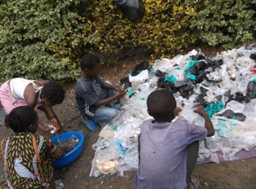 Children collect and sort non-biodegradable garbage from their neighborhood.