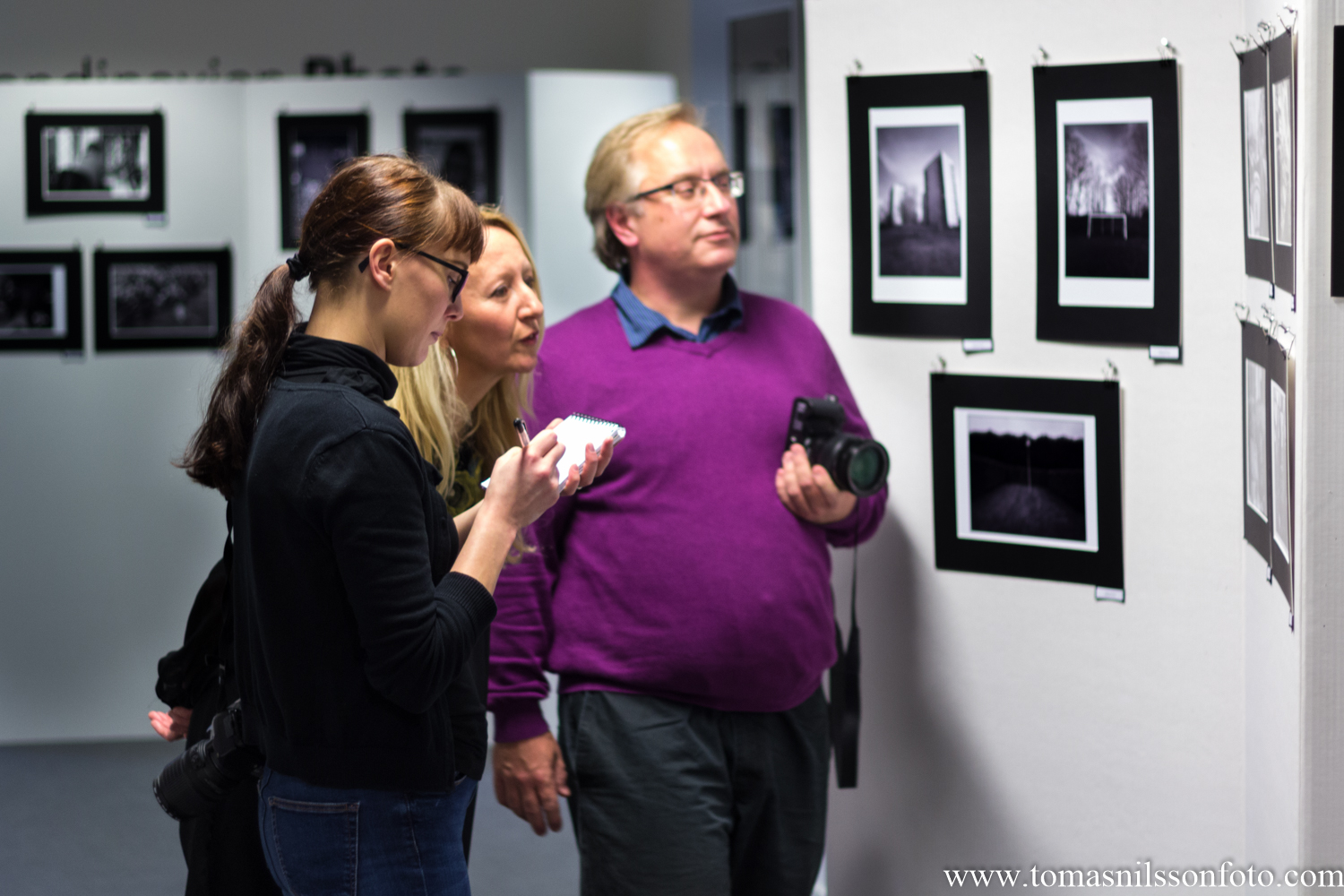 "A reporter from the local paper Skånska Dagbladet talks to Susanne Bogren and the photo club chairman Rikard Persson about the club's anniversary exhibition ""Life in Malmö""."