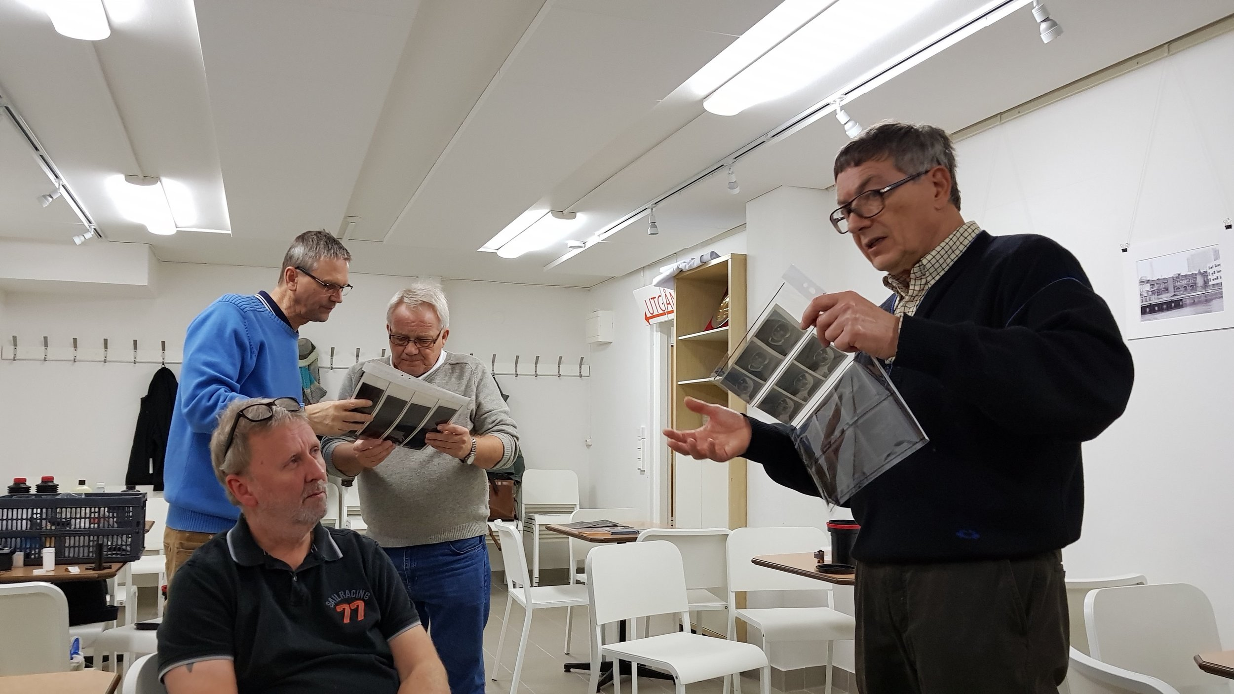Kenneth sharing some negatives with Mikael while Ulf and Kjell studies some contact sheets.