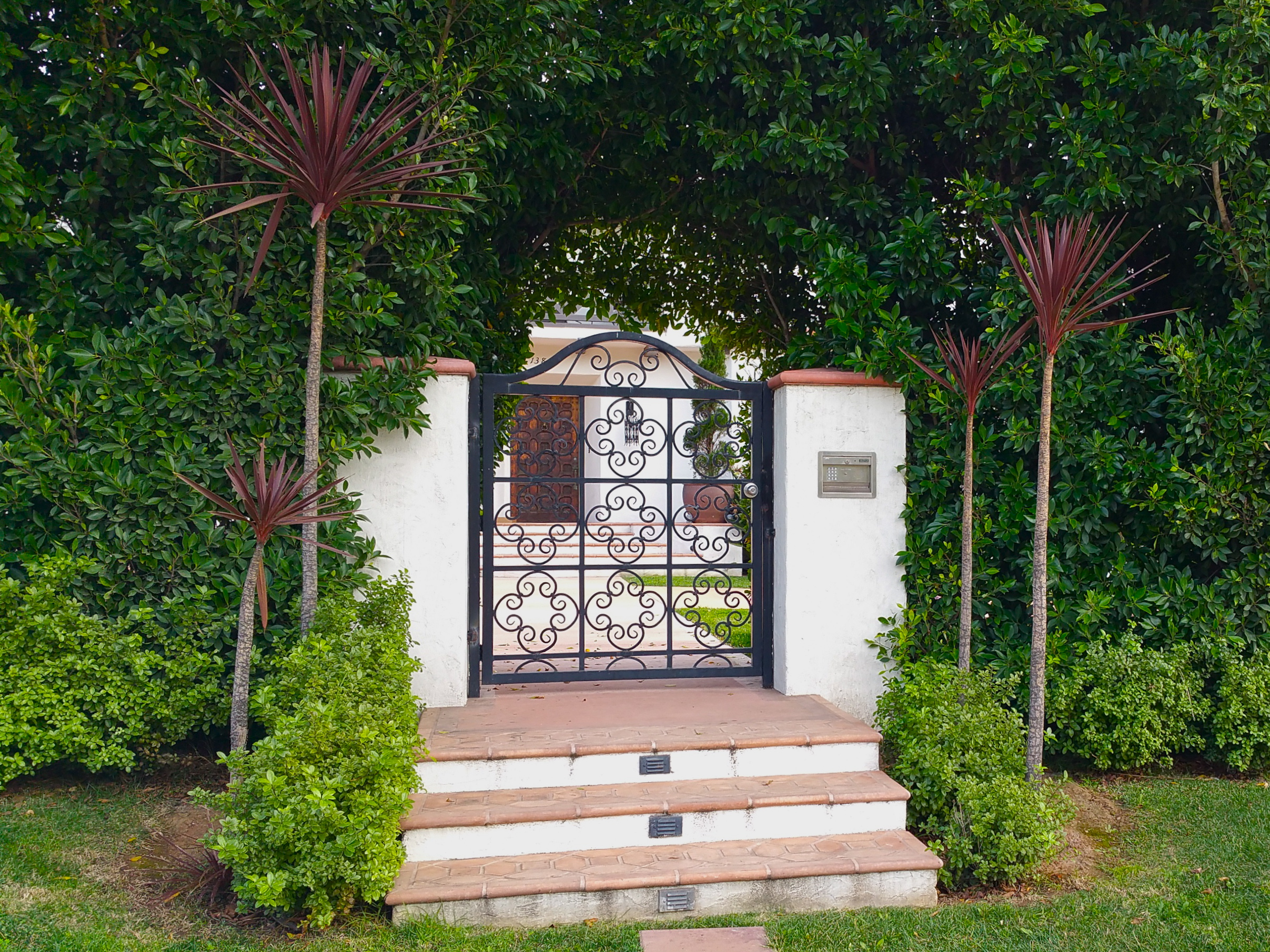 SUNSET - A stately Spanish revival house on a busy street needed a sense of privacy and grandeure to compliment this two story beauty. We planted tall hedges around a custom iron work entrance, added driveway gates, a semicircular driveway with a fountain and appropriate drought tolerant planting to compliment its historic beauty.