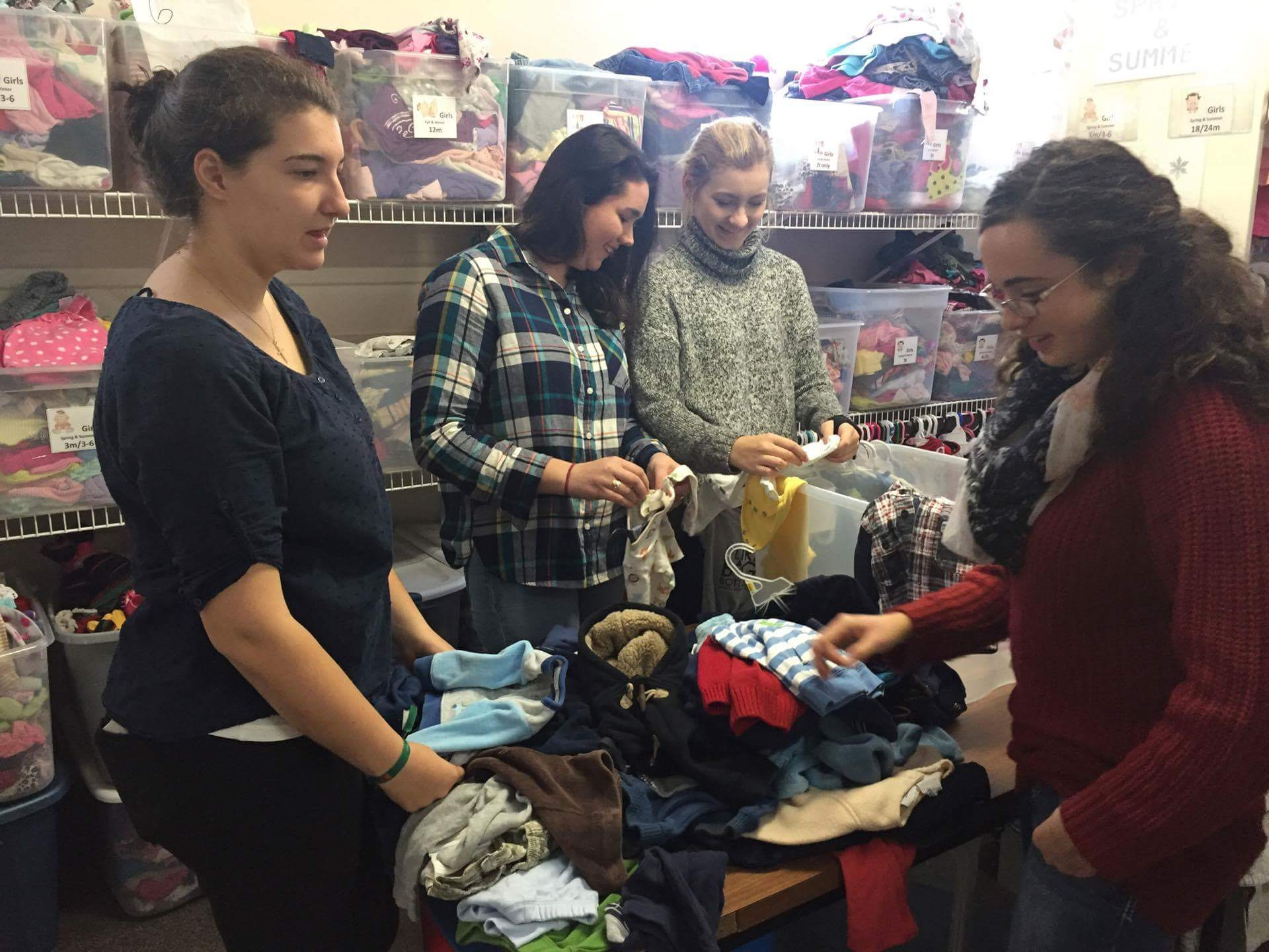the girls are pictured here sorting and hanging baby clothes before they make it into the loving arms boutique.