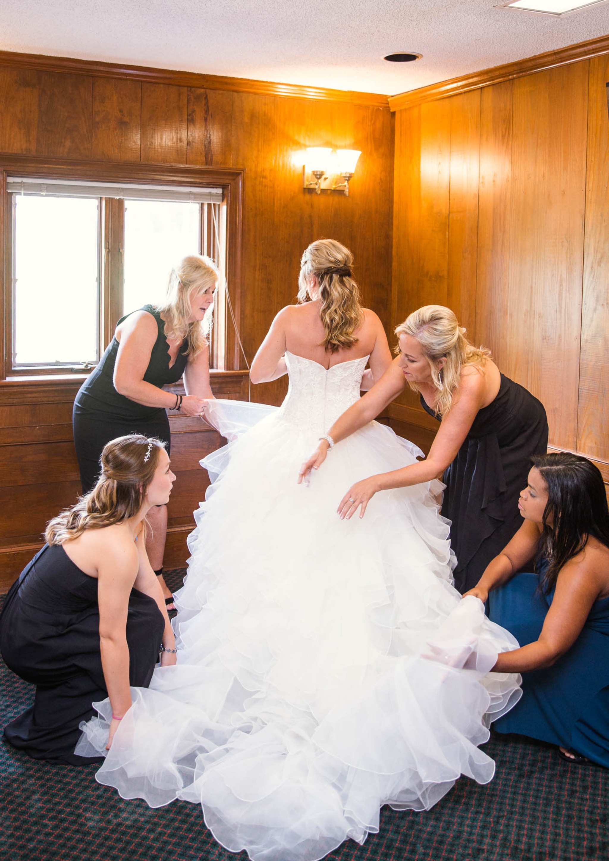 Bridesmaids fluffing the brides ball gown wedding dress - Dona + Doug - MacGregor Downs Country Club in Cary, NC - Raleigh Wedding Photographer